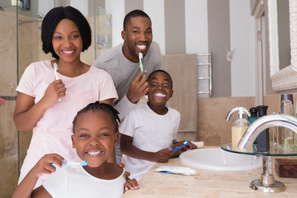 Happy family brushing teeth in bathroom at home