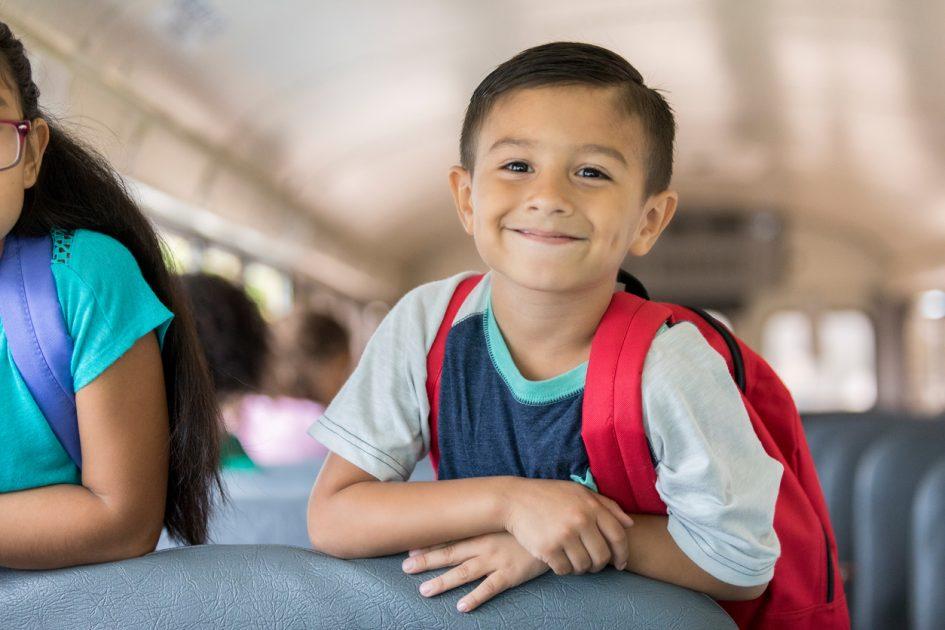 Happy little boy riding a school bus