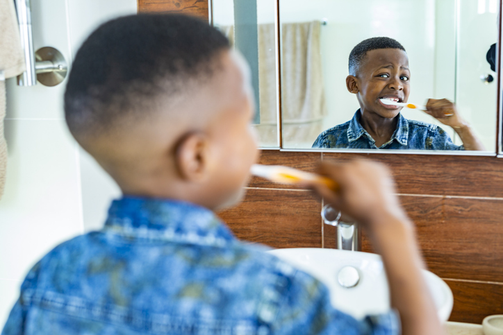 Young African boy brushing his teeth in the morning